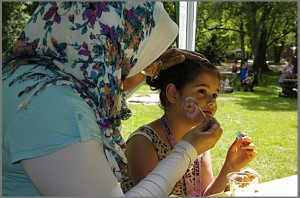 Quartiersrätin Abir Farouk schminckt ein Kind